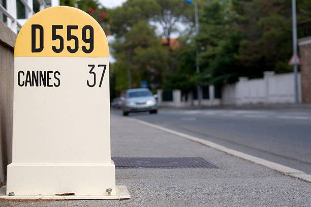 car passing a distance sign to Cannes stock photo