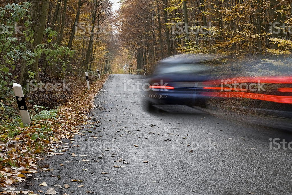 Car passing by on an autumnal forest road royalty-free stock photo