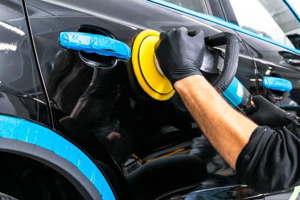 汽車波蘭蠟工人手在拋光前應用保護膠帶。拋光和拋光車。汽車細節。男人握著一把拋光機在手裡擦亮汽車 - 特寫 個照片及圖片檔