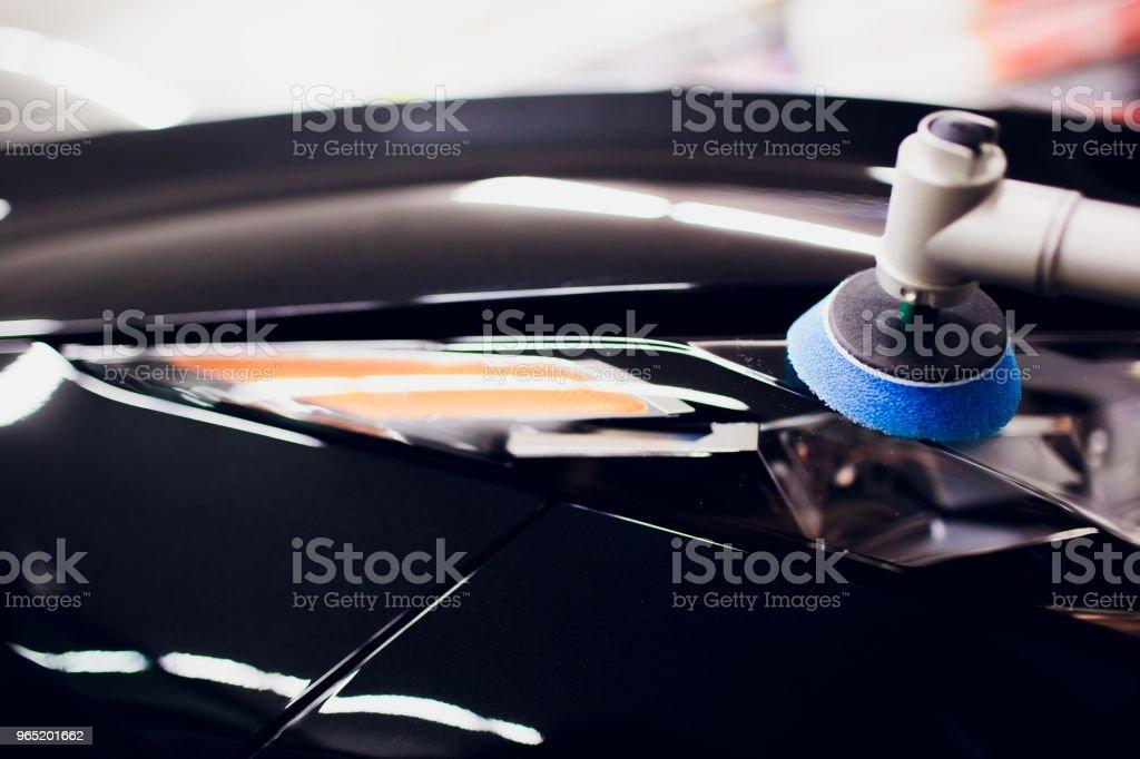 Car polish wax worker hands holding polisher and polish car detailing or valeting concept front yellow orange headlamp auto turn signal zbiór zdjęć royalty-free
