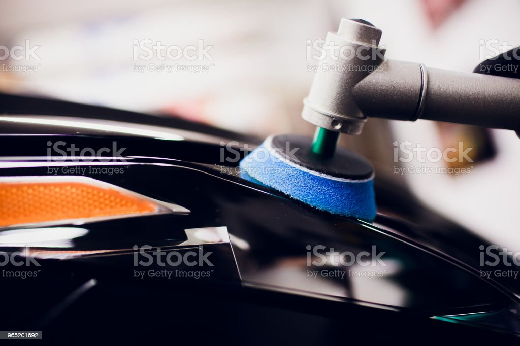Car polish wax worker hands holding polisher and polish car detailing or valeting concept front yellow orange headlamp auto turn signal royalty-free stock photo