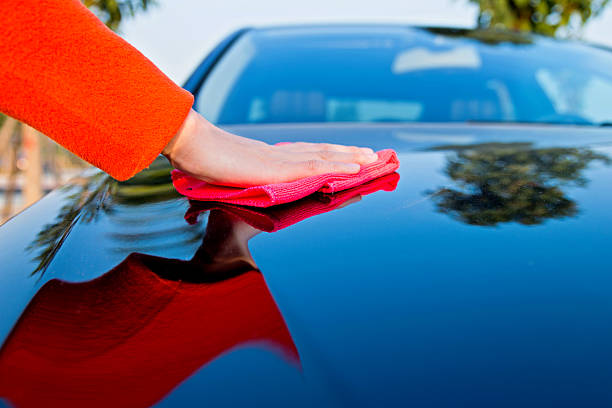 car polishing Woman hand polishing her car. bonnet stock pictures, royalty-free photos & images