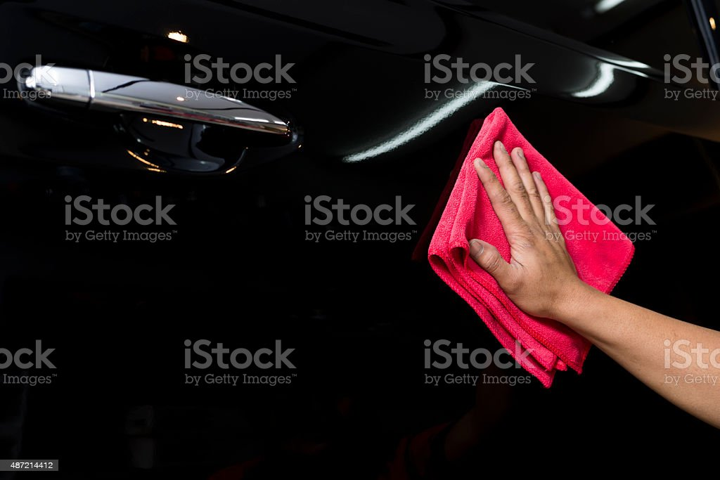Car polishing series : Hand of worker cleaning black car stock photo