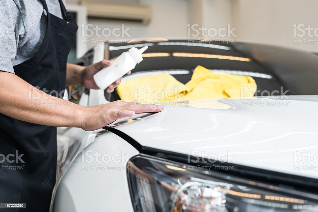 Car polishing series : Worker waxing white car stock photo