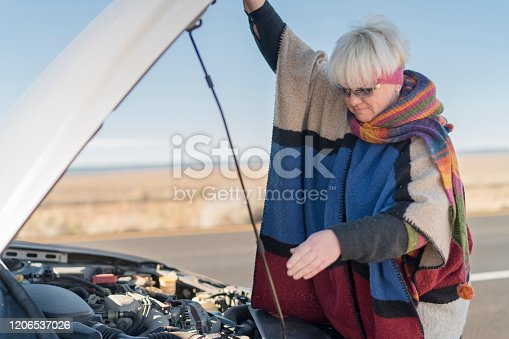 Road accident. The mature positive woman checking the engine.