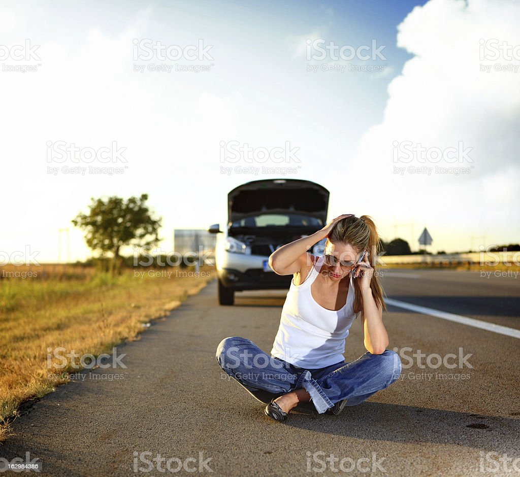 Woman sitting on the road in front of her broken car and making calls