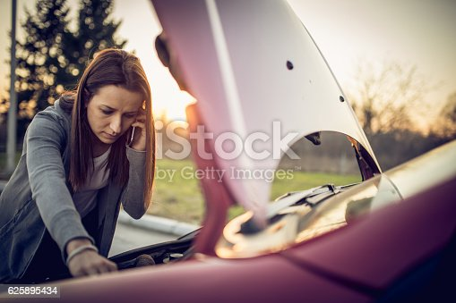 Woman having problem with her car, it stopped on the street. She is calling for help wuth her mobile phone.