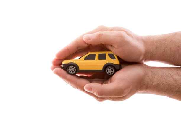 Car protection. Small yellow car covered by hands isolated on white background with clipping path stock photo