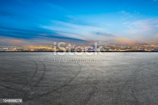 istock Car racing track and modern city skyline with buildings 1048568276