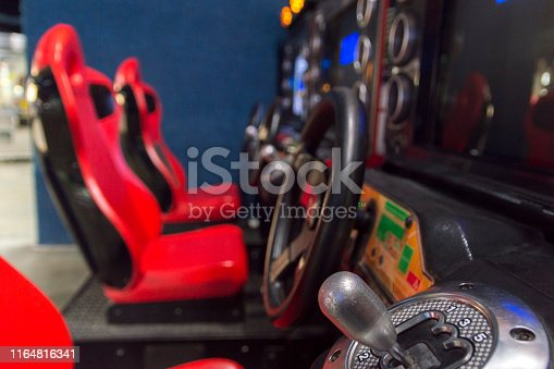 This closeup picture shows the gear shifter and steering wheel for a car racing video game at an arcade.  In the background of the picture are the seats used by video game players.