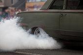 Car make smoke during auto show on street