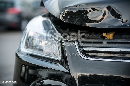Hamburg, Germany - June 28. 2017: Front view of the left part from a black vehicle after a serious rear-end collision in Hamburg, City. The bonnet is heavily deformed and open. the background ist blurred. Neither driver was injured.