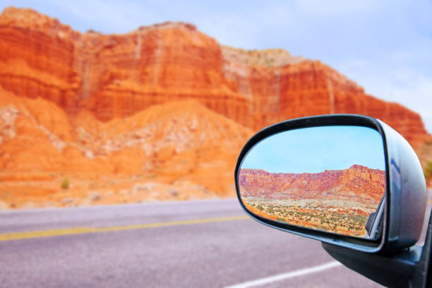 car rearview mirror the Capitol Reef Rocky Mountains looking back in the car's rearview mirror the Capitol Reef Rocky Mountains near escalante utah on route 12 in the united states bending over backwards stock pictures, royalty-free photos & images