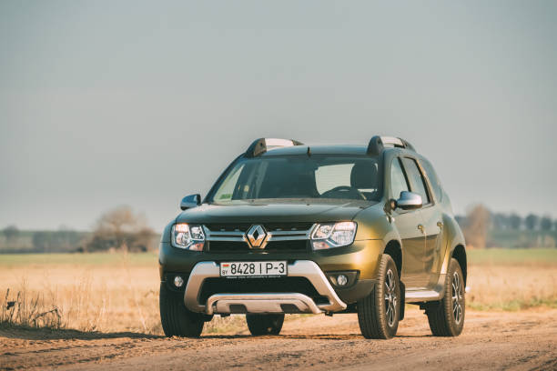 Car Renault Duster Or Dacia Duster Suv Parked On Field Country Road stock photo