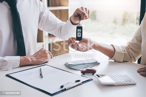 Car rent agent manager holding key of new car giving to woman client after signing good deal agreement contract, renting considering vehicle.