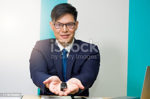 936987338 istock photo A car rental owner or car dealer wearing a blue suit and glasses is showing gestures of delivering keys with open the palm to invite customers at the counter in modern showroom. 1176785897