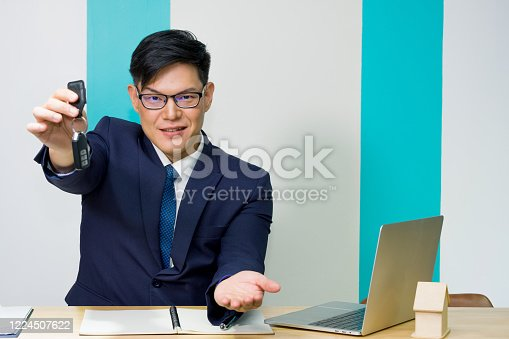 936987338 istock photo A car rental owner or car dealer wearing a blue suit and glasses is showing gestures of delivering keys with open the palm to invite customers at the counter in modern showroom. 1224507622