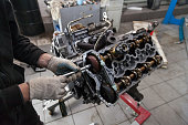 istock A car repair and maintenance specialist unscrews a bolt with a wrench on an 8-cylinder engine in a workshop. Auto service industry. 1177368347