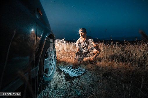 627511482 istock photo Car repair. Lucky me. Changing car tire in the middle of nowhere at dusk. DIY 1172402747