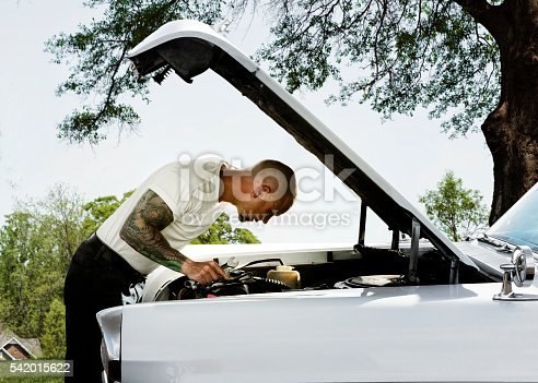 Man with raised hood up on vintage car working on motor.