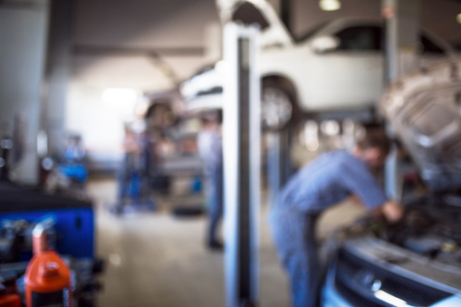 Car repair service in defocus, industrial background. Cars on lifts, transport service area, the mechanic repairs the car. Copy space