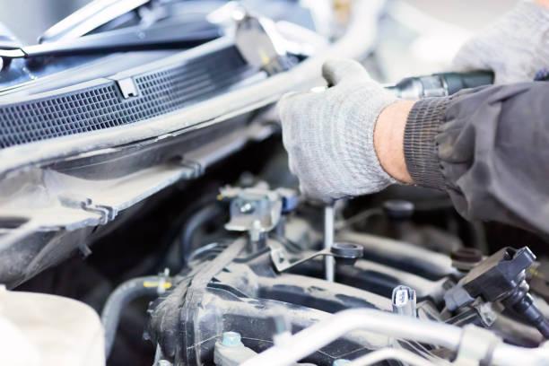 auto-reparatur-service. mechaniker arbeitet mit einem auto in der mechanischen werkstatt - garagen pergola stock-fotos und bilder