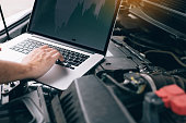 istock Car repair technicians use laptop computers to measure engine values for analysis. 1160674360
