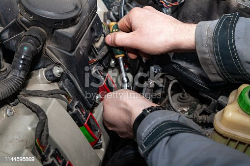 A car repairman unscrews parts with a wrench with a green handle in the engine compartment such as spark plugs and ignition coils in a vehicle repair workshop. Auto service industry.