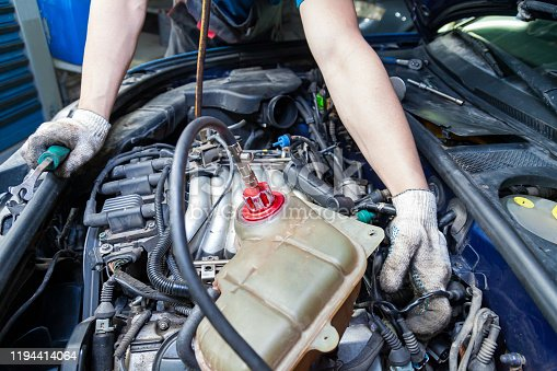 A car repairman unscrews parts with a wrench with a green handle in the engine compartment suh as spark plugs and ignition coils in a vehicle repair workshop. Auto service industry.
