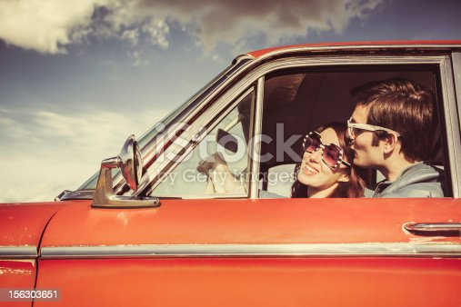 A young man kisses his girlfriend wearing white sunglasses, visible through the driver window of their classic 1960s car.  Vintage styling and colors.  Wide and low angle to emphasis the blue sky and clouds.  Horizontal with copy space.