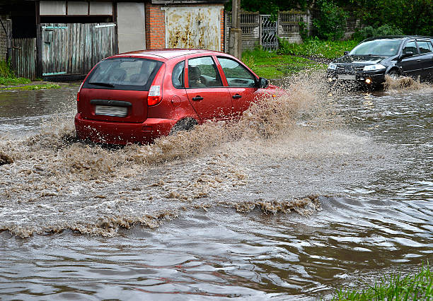 car rides in heavy rain on a flooded road - impaired driving stock photos and pictures