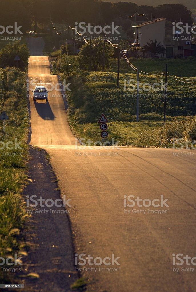 car running on asphalt downhill at sunset royalty-free stock photo