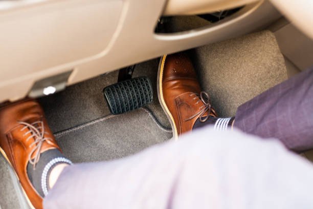 car safety system on the feet Accident and brake, danger of auto motor-driven bikes, driving habits Closeup of a thirties man wearing brown shoes carrying a car accelerator and a brake / car safety system on the feet Accident and brake, danger of auto motor-driven bikes, driving habits vehicle clutch stock pictures, royalty-free photos & images