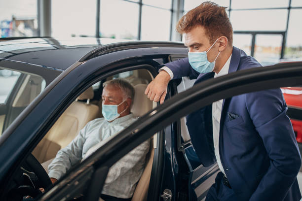Car saleperson with protective face mask showing a car to senior male customer stock photo