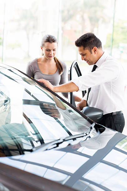 car sales consultant showing a new car to potential buyer stock photo