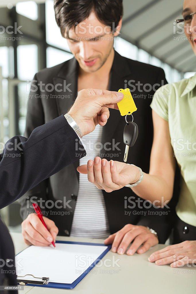 Car sales - dealer handing woman auto key stock photo