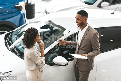 Car Sales Manager Showing Auto To Afro Lady Buyer Standing In Luxury Automobile Dealership Store. Buying Vehicle Concept