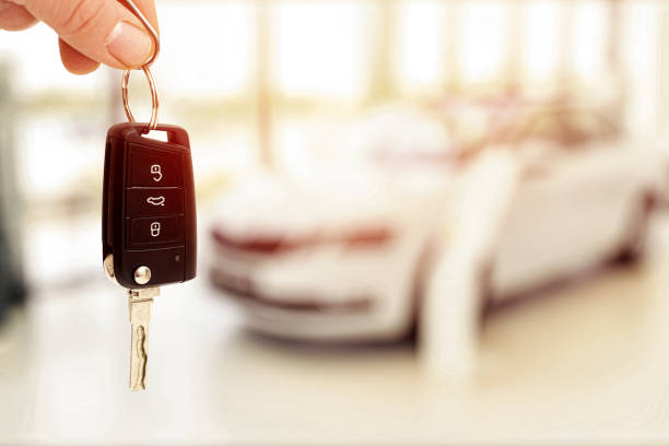 car sales showroom and person holding car key in hands stock photo