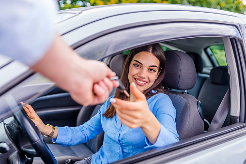 istock Car salesman giving key to new owner or customer 1011173074