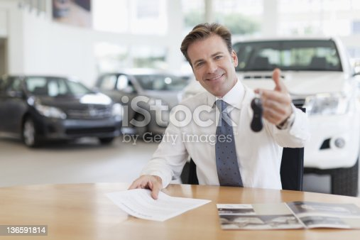 1138561232 istock photo Car salesman handing keys over desk 136591814