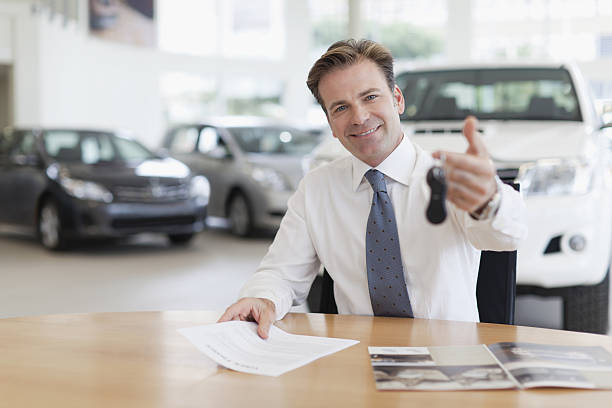 Car salesman handing keys over desk  car salesperson stock pictures, royalty-free photos & images