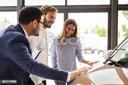 988321834 istock photo Car salesman making a sale to a young couple 984018966