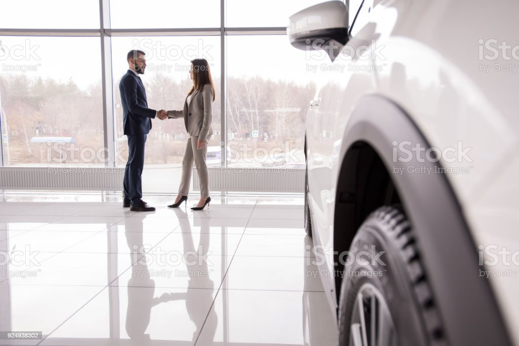 Car Salesman Shaking Hands with Customer Wide angle portrait of car salesman shaking hands with woman buying new car in dealership showroom, car wheel in foreground, copy space Adult Stock Photo