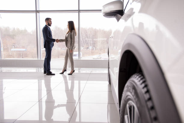 Car Salesman Shaking Hands with Customer Wide angle portrait of car salesman shaking hands with woman buying new car in dealership showroom, car wheel in foreground, copy space car salesperson stock pictures, royalty-free photos & images