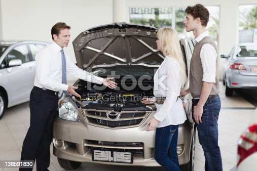 136591850 istock photo Car salesman showing engine to customers 136591830