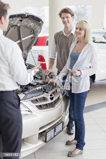 136591850 istock photo Car salesman showing engine to customers 136591831