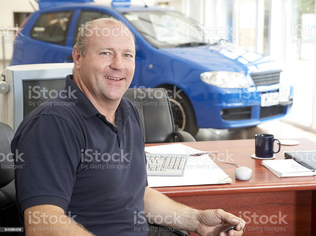 Car salesman sitting in showroom royalty-free stock photo