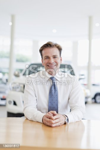 1138561232 istock photo Car salesman smiling at desk 136591812