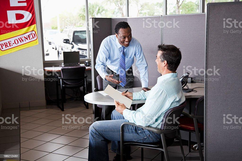 Car salesman with customer royalty-free stock photo