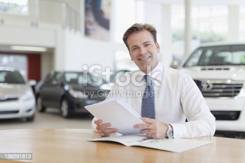 1138561232 istock photo Car salesman with paperwork at desk 136591813